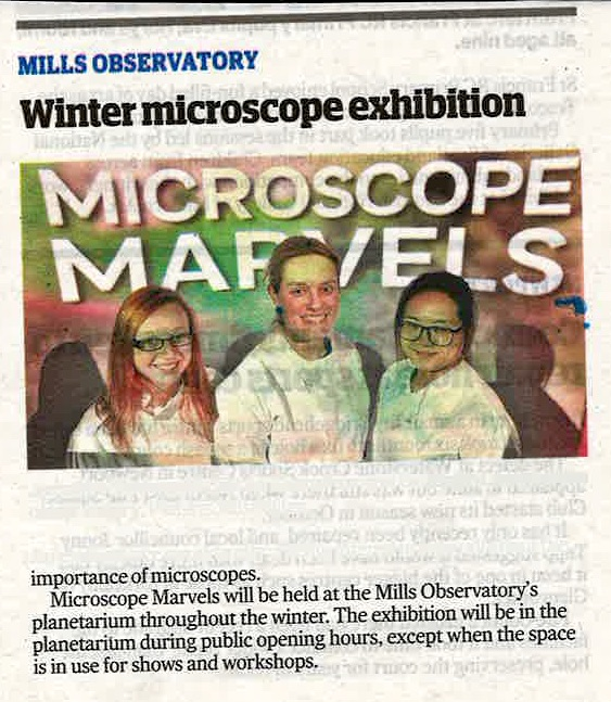 """Newspaper clipping, photo of 3 female scientists in front of presentation screen """"Microscope Marvels"""""""