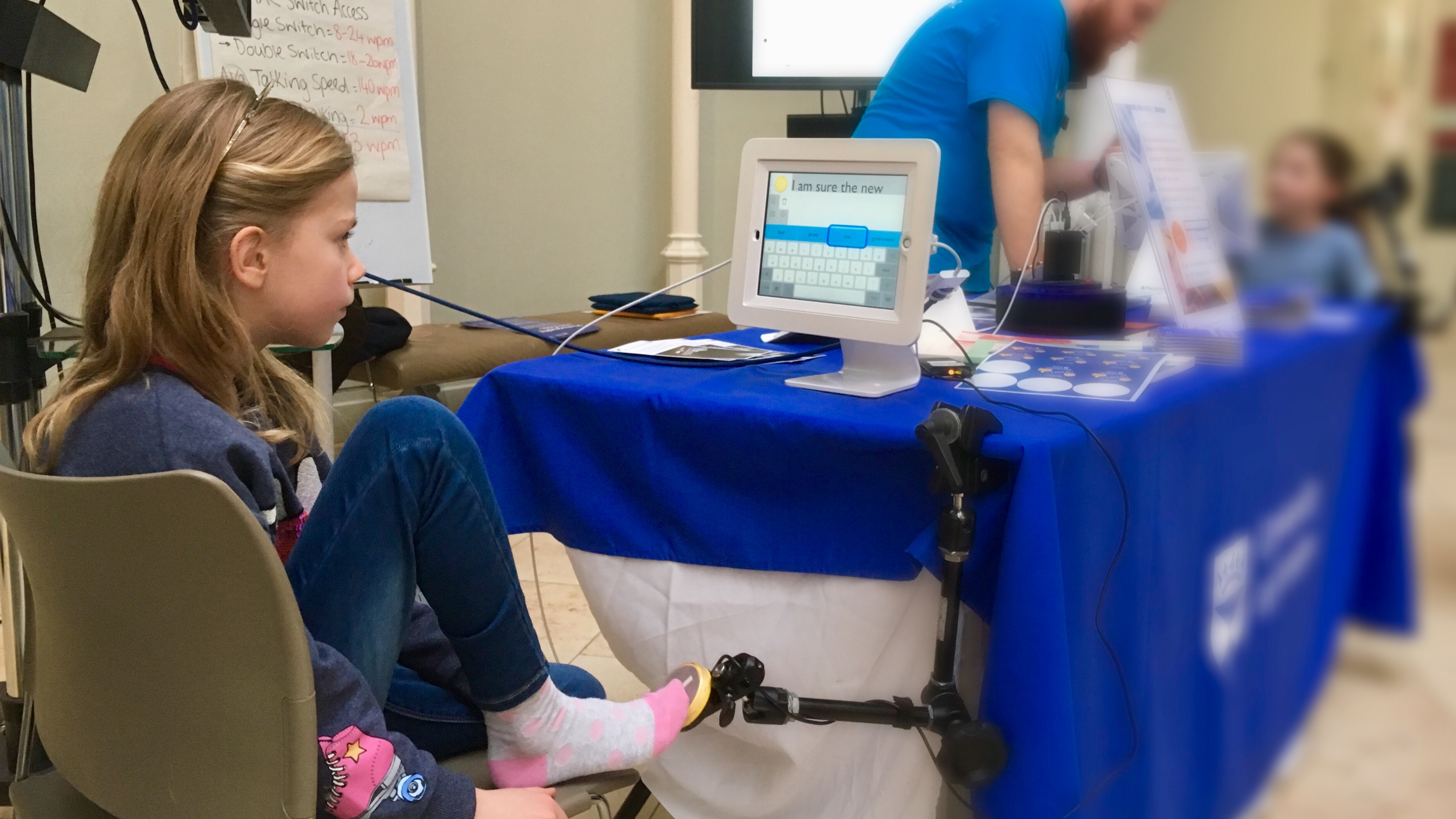 A girl tries switch scanning using her toe to access an iPad with a communication app.