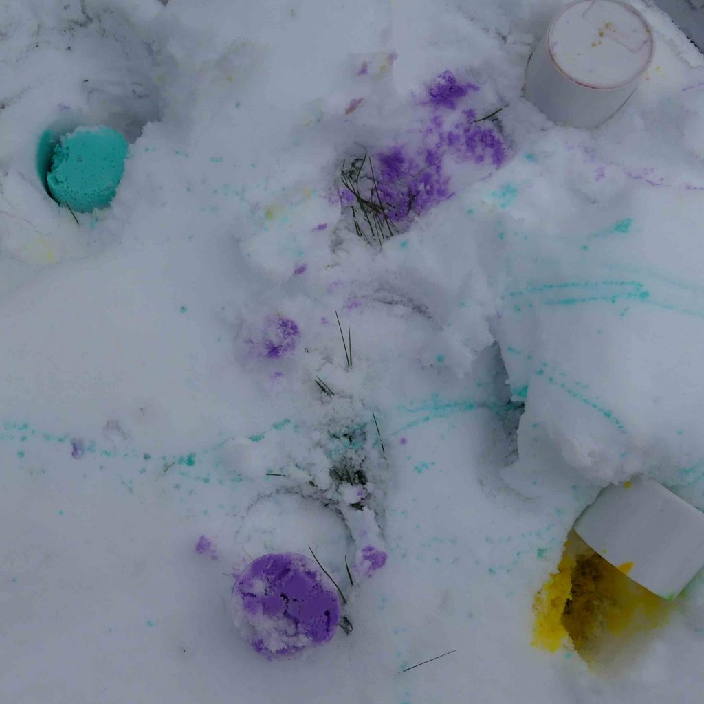 coloured paint poured onto snow