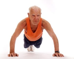 An older man wearing an orange vest holds a strong press-up pose