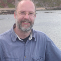 photo of Burkhard in front of shoreline, he is smiling, he has a beard and is wearing glasses