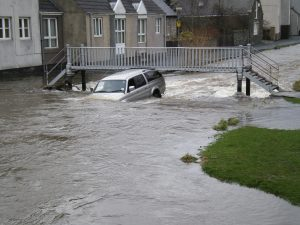 Car under footbridge during floods